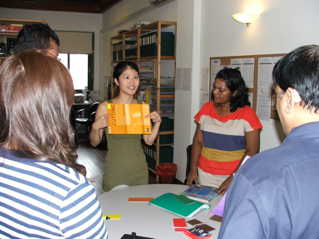 Diploma in TESOL trainees discussing English teaching course books
